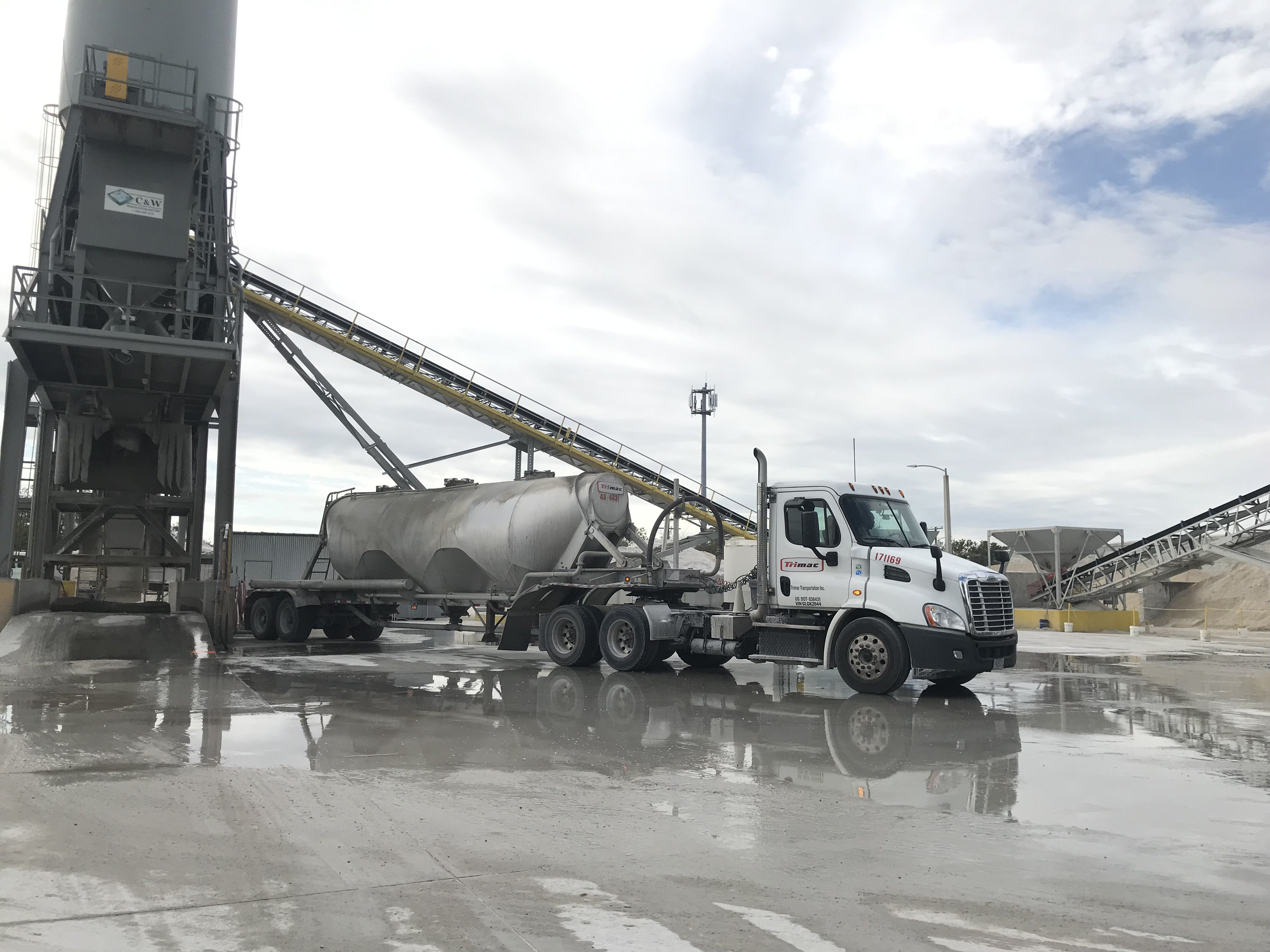 A bulk solids truck makes a delivery to a ready-mix cement plant.