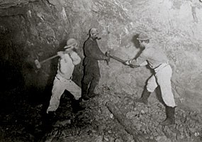 A photo of three miners drilling a hole in a mine.